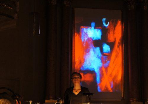 Solgerd Isalv vor dem Lichtbühnenbild 'Entfachte Debatte' von Petra Annemarie Schleifenheimer in der Auferstehungskirche Fürth